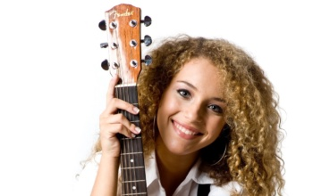 An attractive young teenage woman with an acoustic guitar on white background